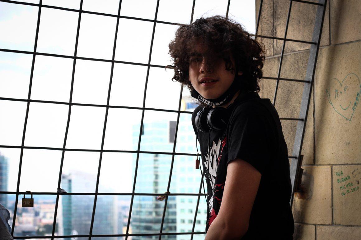 nastolatek, długie włosy, słuchawki na szyi